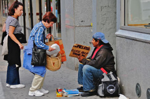 "This was taken about halfway up the block on the east side of Broadway, between 79th and 80th Street. It's at the north end of the ""Filene's Basement"" store on the corner, and it's a place where I've often seen homeless people holding up a sign that asks for assistance... With very rare exceptions, I haven't photographed these homeless people; it seems to me that they're in a very defensive situation, and I don't want to take advantage of their situation. But something unusual was happening here: the two women (who were actually cooperating, and acting in tandem, despite the rather negative demeanor of the woman on the left) were giving several parcels of food to the young homeless man on the right. I don't know if the women were bringing food from their own kitchen, or whether they had brought it from a nearby restaurant. But it was obviously a conscious, deliberate activity, and one they had thousght about for some time... What was particularly interesting was that they didn't dwell, didn't try to have a conversation with the young man;they gave him they food they had brought, and promptly walked away. As they left, I noticed the young man peering into his bag (the one you see on the ground beside him in this picture) to get a better sense of the delicious meal these two kind women had brought him... ********************** This is part of an evolving photo-project, which will probably continue throughout the summer of 2008, and perhaps beyond: a random collection of ""interesting"" people in a broad stretch of the Upper West Side of Manhattan -- between 72nd Street and 104th Street, especially along Broadway and Amsterdam Avenue. I don't like to intrude on people's privacy, so I normally use a telephoto lens in order to photograph them while they're still 50-100 feet away from me; but that means I have to continue focusing my attention on the people and activities half a block away, rather than on what's right in front of me. I've also learned that, in many cases, the opportunities for an interesting picture are very fleeting -- literally a matter of a couple of seconds, before the person(s) in question move on, turn away, or stop doing whatever was interesting. So I've learned to keep the camera switched on (which contradicts my traditional urge to conserve battery power), and not worry so much about zooming in for a perfectly-framed picture ... after all, once the digital image is uploaded to my computer, it's pretty trivial to crop out the parts unrelated to the main subject. For the most part, I've deliberately avoided photographing bums, drunks, drunks, and crazy people. There are a few of them around, and they would certainly create some dramatic pictures; but they generally don't want to be photographed, and I don't want to feel like I'm taking advantage of them. I'm still looking for opportunities to take some ""sympathetic"" pictures of such people, which might inspire others to reach out and help them. We'll see how it goes ... The only other thing I've noticed, thus far, is that while there are lots of interesting people to photograph, there are far, far, *far* more people who are *not* so interesting. They're probably fine people, and they might even be more interesting than the ones I've photographed ... but there was just nothing memorable about them."