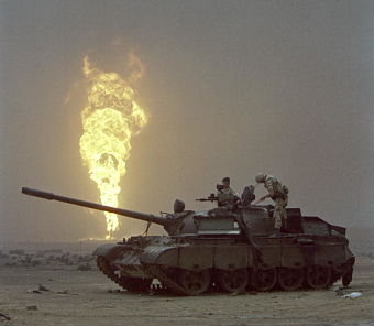 Burning oil-wells at Al Magwa with a destroyed Iraqi tank in the foreground. The Iraqi destruction has caused tremendous damage to the region's environment.